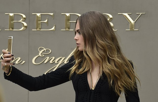 British model Cara Delevingne takes a selfie as she arrives for the Burberry Spring/Summer 2016 collection during London Fashion Week September 21, 2015. (Photo by Toby Melville/Reuters)
