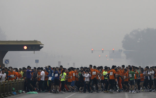 Runners jog past Chang'an Avenue near Tiananmen Square shrouded in haze at the start of 2014 Beijing International Marathon in Beijing, China Sunday, October 19, 2014. (Photo by Andy Wong/AP Photo)