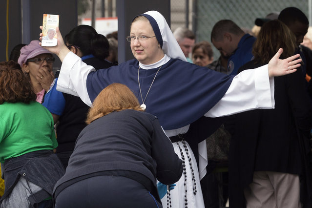 A nun from The Sisters of Life, of New York City, is inspected at a security checkpoint as she arrives for a Mass to be celebrated by Pope Francis, Sunday, September 27, 2015, in Philadelphia. Pope Francis will end the final day of his three-city U.S. tour with the Mass on Philadelphia's grandest boulevard, the Benjamin Franklin Parkway. (Photo by John Minchillo/AP Photo)