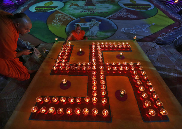 """Hindu priests light oil lamps in a formation of the """"Swastika"""", a Hindu symbol of peace, a day before the Hindu festival of Diwali in Ahmedabad October 22, 2014. (Photo by Amit Dave/Reuters)"""
