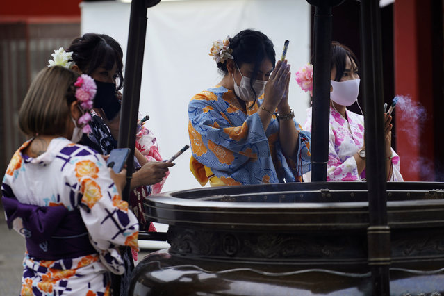 A restaurant employee wearing a protective face mask to help curb the spread of the coronavirus offer a joss sticks on a huge incense burner in the Asakusa district in Tokyo Monday, July 27, 2020. The Japanese capital confirmed Monday more than 100 new coronavirus cases. (Photo by Eugene Hoshiko/AP Photo)