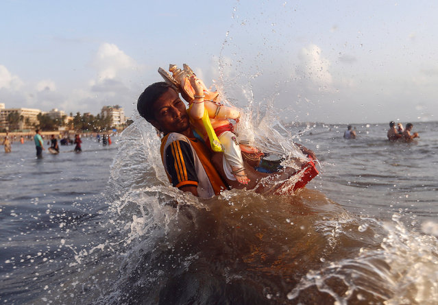 A devotee carries an idol of the Hindu god Ganesh, the deity of prosperity, into the Arabian Sea on the second day of Ganesh Chaturthi festival in Mumbai, India, September 6, 2016. (Photo by Danish Siddiqui/Reuters)