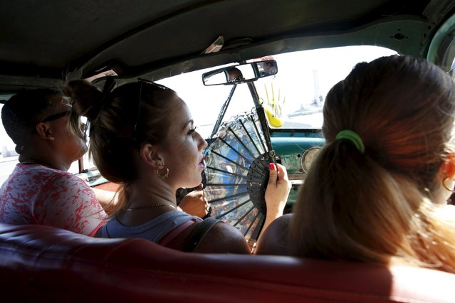 A woman fans herself while riding in a taxi in Havana, Cuba September 19, 2015. (Photo by Carlos Garcia Rawlins/Reuters)
