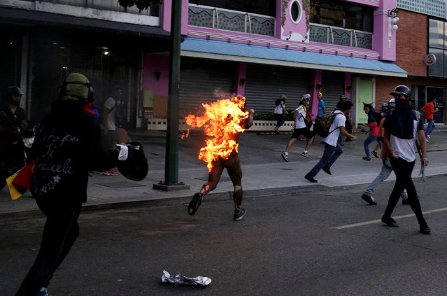 A man who was set on fire by people accusing him of stealing during a rally against Venezuela's President Nicolas Maduro runs amidst opposition supporters in Caracas, Venezuela, May 20, 2017. (Photo by Marco Bello/Reuters)
