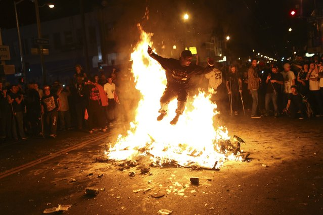 A man jumps through a fire along a street in the Mission District during a celebration after the San Francisco Giants defeated the Kansas City Royals in Game 7 of the World Series, in San Francisco, California October 29, 2014. (Photo by Robert Galbraith/Reuters)