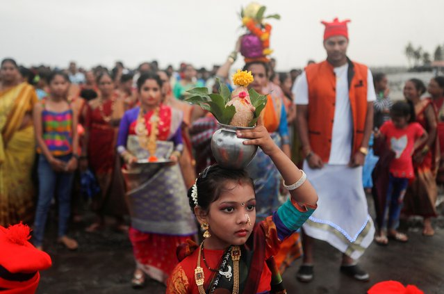 A girl carries a coconut in a vessel on her head during a procession for Narali Purnima or coconut festival amidst the spread of the coronavirus disease (COVID-19) in Mumbai, India, August 3, 2020. (Photo by Francis Mascarenhas/Reuters)