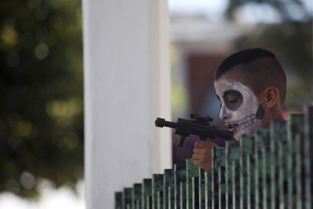 """A boy with his face painted as a skulls plays with a toy gun during the start of the """"Las Catrinas"""" festival,  ahead of the Day of the Dead in Cupula on the outskirts of Morelia, October 26, 2014. La Catrina is a popular figure in Mexico known as """"The Elegant Skull"""". The annual Day of the Dead is observed on November 1 and 2.  REUTERS/Alan Ortega (MEXICO - Tags: RELIGION SOCIETY TRAVEL)"""