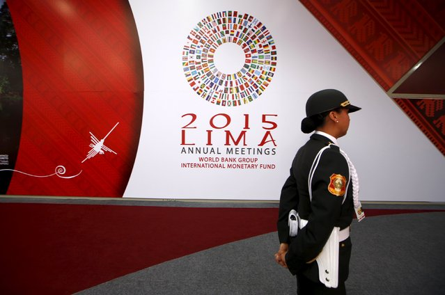 A Peruvian policewoman walks past a welcome sign to the 2015 IMF/World Bank annual meetings at the venue of the event in Lima, October 5, 2015. (Photo by Mariana Bazo/Reuters)