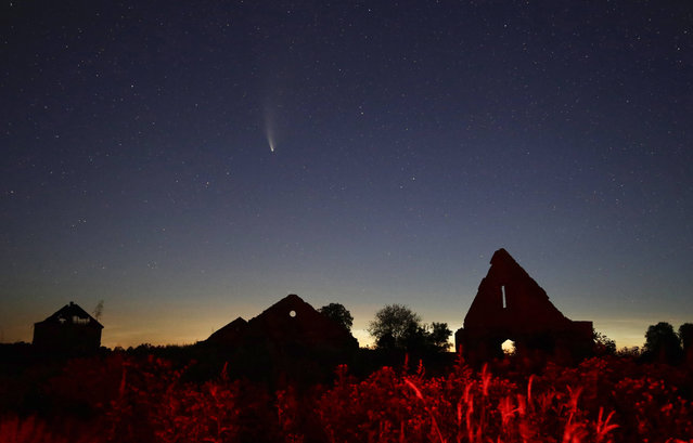 The comet Neowise or C/2020 F3 is seen behind the ruins of a medieval castle near the village of Shchorsy, 130 kilometers (81 miles) west of capital Minsk, Belarus, early Wednesday, July 22, 2020. (Photo by Sergei Grits/AP Photo)