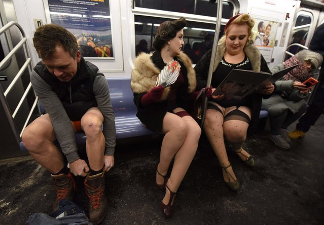"""Participants in the 17 th Annual """"No Pants Subway Ride"""" ride the New York City subway on January 7, 2018 in New York. (Photo by Timothy A. Clary/AFP Photo)"""