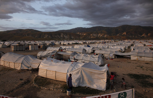 Earthquake victims sheltered at Camp Corail, a provisional camp about 12 miles (20 km) north of Port-au-Prince, walk among their tents November 1, 2010. (Photo by Eduardo Munoz/Reuters)
