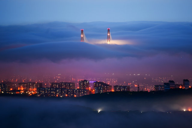 "The towers of Russky Bridge are seen over the fog covered Vladivostok, Russia on May 26, 2020. The so-called ""fog season"" on the Pacific coast and in the south of Russia's Primorye Territory lasts from April till September. (Photo by Yuri Smityuk/TASS)"