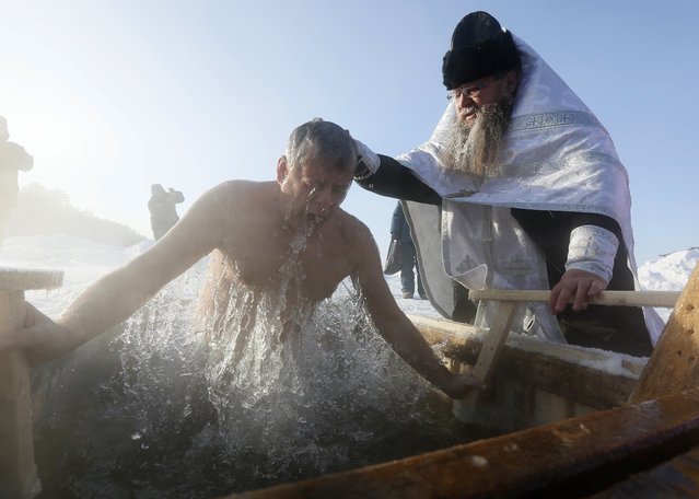 Priest Sergei Ryzhov conducts a ceremony as a man takes a dip in the freezing waters of Lake Buzim during Orthodox Epiphany celebrations, with the air temperature at about minus 40 degrees Fahrenheit (minus 40 degrees Celsius), near the village of Sukhobuzimskoye north of Krasnoyarsk, Russia on January 19, 2018. (Photo by Ilya Naymushin/Reuters)