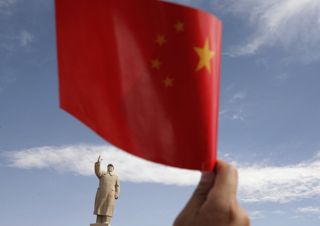 A spectator waves a Chinese flag in front of a statue of Chairman Mao Zedong in Kashgar, Xinjiang province. (Photo by Reinhard Krause/Reuters)