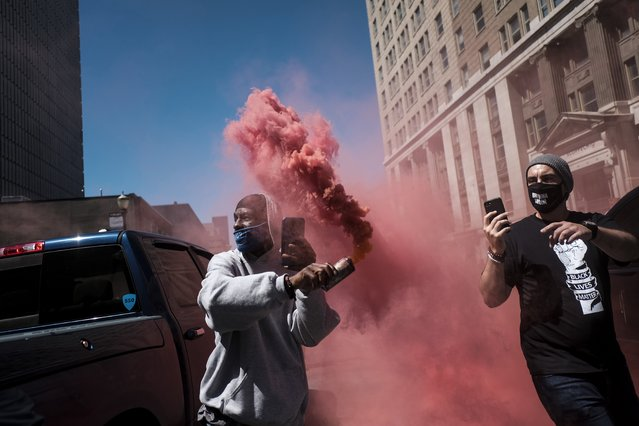 """A demonstrator throws back a colored smoke grenade during dueling protests outside of the Louisville Court House in Louisville, Kentucky, U.S., on Saturday, Sept. 5, 2020. Various groups of protesters gathered in Louisville on Saturday, including members of a self-described """"patriot"""" militia and those protesting the killing of Breonna Taylor, ahead of larger demonstration planned outside the Kentucky Derby horse race. (Photo by Matthew Hatcher/Bloomberg via Getty Images)"""