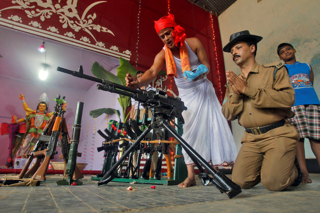 A police officer has weapons blessed by a Hindu priest during the Vishwakarma Puja festival in the outskirts of Agartala, India, September 17, 2016. (Photo by Jayanta Dey/Reuters)