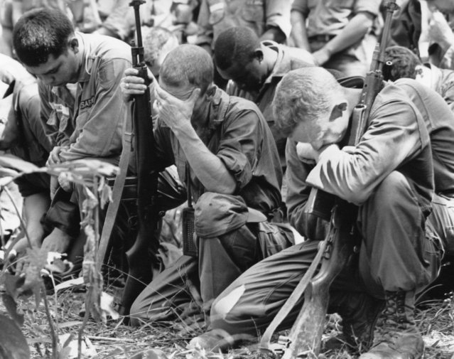 U.S. infantrymen pray in the Vietnamese jungle December 9, 1965 during memorial services for comrades killed in the battle of the Michelin rubber plantation, 45 miles northwest of Saigon. (Photo by Horst Faas/AP Photo)