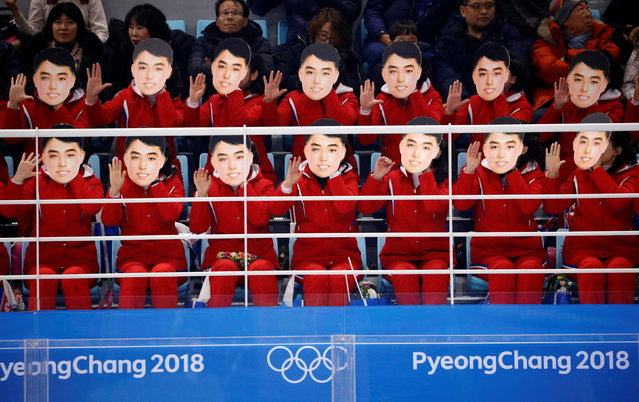 """A photo taken on February 10, 2018 shows North Korean cheerleaders wearing masks as they perform during the women' s preliminary round ice hockey match between the unified Korea team and Switzerland at the Pyeongchang 2018 Winter Olympics, at the Gangneung Ice Arena in Gangneung. According to Yonhap, South Korea' s unification ministry has denied reports that the masks featured the image of North Korea' s late founding leader Kim Il- sung. The masks were worn as the cheerleaders sang """"Whistle"""", a North Korean song whose lyrics are about a man' s unrequited love for a female neighbor. (Photo by Brian Snyder/Reuters)"""