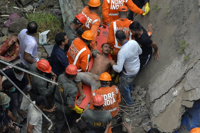 A man is rescued from the debris after a residential building collapsed in Bhiwandi in Thane district, a suburb of Mumbai, India, Monday, September 21, 2020. (Photo by Praful Gangurde/AP Photo)