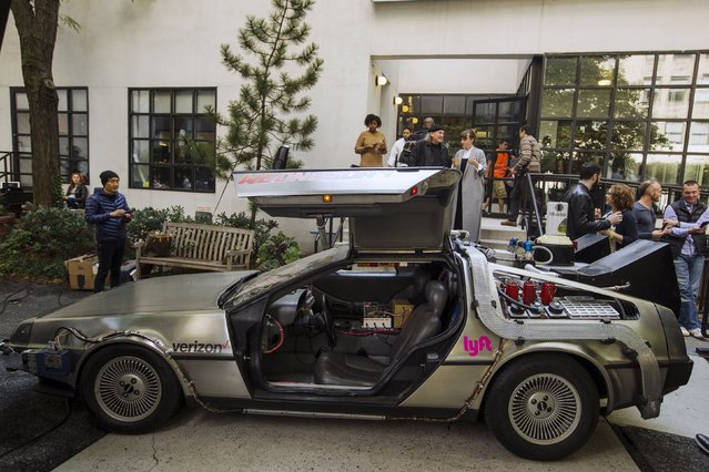 "Pedestrians stop to look at and photograph a DeLorean Motor Company DMC-12 customized to look identical to the car used in the film ""Back to the Future Part II"" and that will be part of a Lyft promotion in New York, October 21, 2015. (Photo by Lucas Jackson/Reuters)"