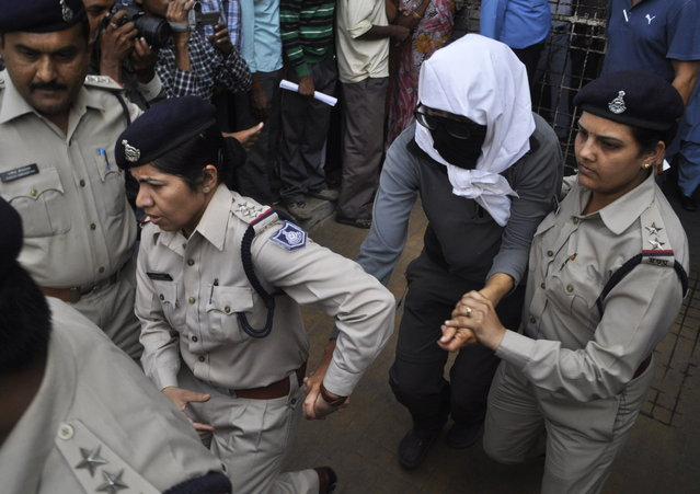 A Swiss woman with her face covered is taken to a hospital by police for her medical examination at Gwalior in the central Indian state of Madhya Pradesh March 16, 2013. Four men raped a 39-year-old Swiss woman camping with her husband in an Indian forest, police said on Saturday, turning the spotlight anew on the security of women in the world's largest democracy. (Photo by Reuters/Stringer)