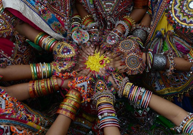 "Indian folk dancers from the Panghat Group of Performing Arts pose for a photograph during a dress rehearsal for an event to mark the forthcoming Hindu festival ""Navaratri"", or the Festival of Nine Nights, in Ahmedabad, India, September 25, 2016. The Navaratri festival begins on October 1. (Photo by Sam Panthakysam Panthaky/AFP Photo)"