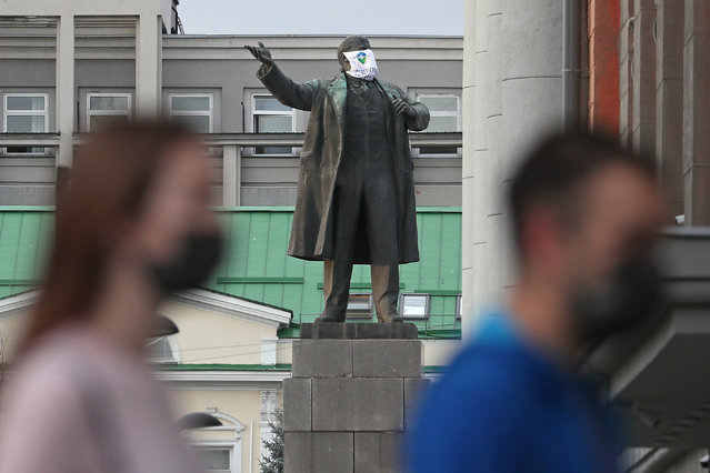 """A statue of Vladimir Lenin in 1905 Goda Square in Yekaterinburg, Russia on October 14, 2020, with a face mask put on and signed """"Protect Yourself and the Ones You Love"""". A group of medical volunteers has put face masks on local statues with consent from the authorities. (Photo by Donat Sorokin/TASS)"""