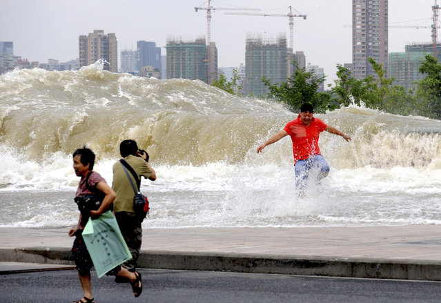 A man takes pictures as visitors run away from a wave caused by a tidal bore which surged past a barrier on the banks of Qiantang River, in Hangzhou, Zhejiang province, August 14, 2014. (Photo by Reuters/Stringer)