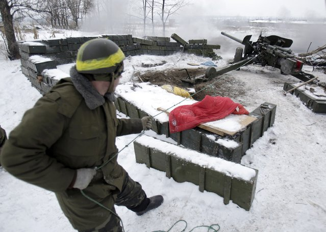 A Ukrainian serviceman fires a cannon positioned close to the airport in the eastern Ukranian city of Donetsk on December 2, 2014. Ukraine and pro-Russian separatists agreed Tuesday to a truce at Donetsk airport – ground zero in a war that has killed more than 4,000 people – as well as across a wider swathe of rebel-held territory. (Photo by Anatolii Stepanov/AFP Photo)