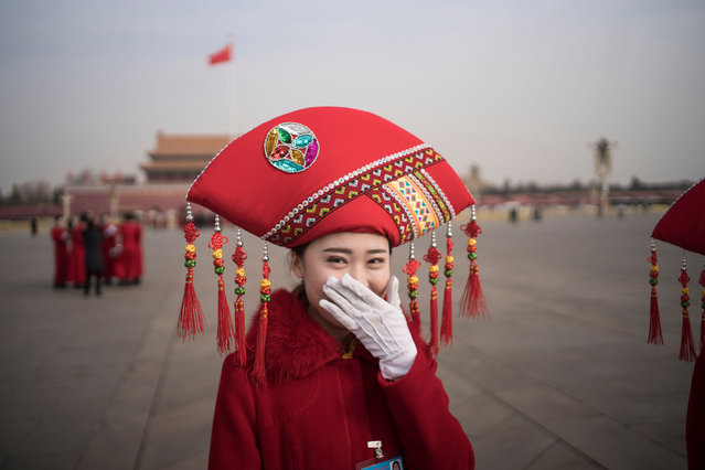 A Chinese hostess reacts at Tiananmen square during the opening session of the National People's Congress, China's legislature, in Beijing on March 5, 2018. China's rubber-stamp parliament opens a major annual session set to expand President Xi Jinping's considerable power and clear him a path towards lifelong rule. (Photo by Fred Dufour/AFP Photo)