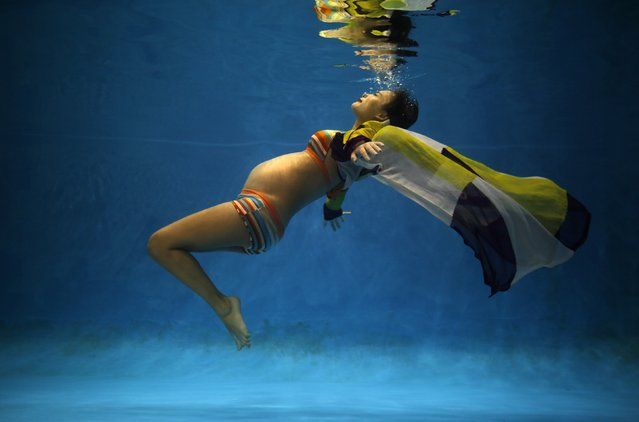Jiejin Qiu, who is six months pregnant with her first baby, poses underwater during a photo shoot at a local wedding photo studio in Shanghai, in this September 5, 2014 file photo. (Photo by Carlos Barria/Reuters)