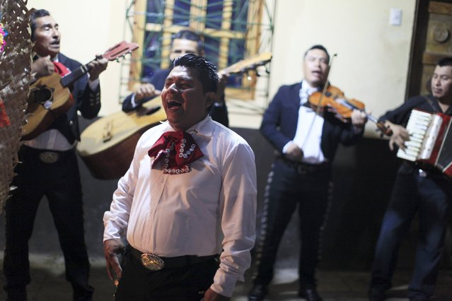 """A mariachi group performs at a family altar during the celebration of """"Los Canchules"""" in Nahuizalco November 1, 2015. (Photo by Jose Cabezas/Reuters)"""