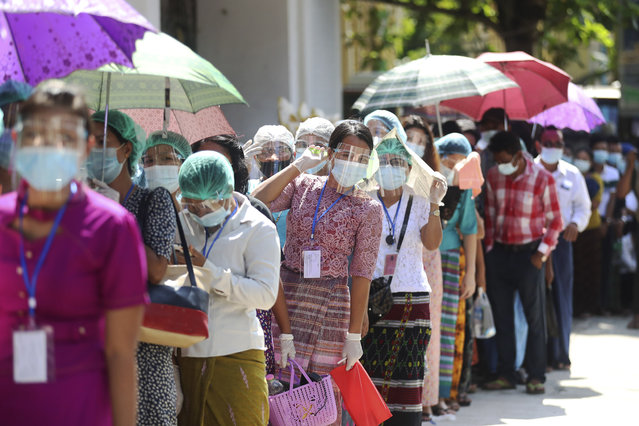 Voters wearing protective face masks to help curb the spread of the coronavirus line up to cast their ballots at a polling station near Shwedagon pagoda Sunday, November 8, 2020, in Yangon, Myanmar. Voting was underway in Myanmar's elections on Sunday, with the party of Nobel Peace Prize laureate Aung San Suu Kyi heavily favored to retain power it had wrestled from the powerful military five years ago. (Photo by Thein Zaw/AP Photo)