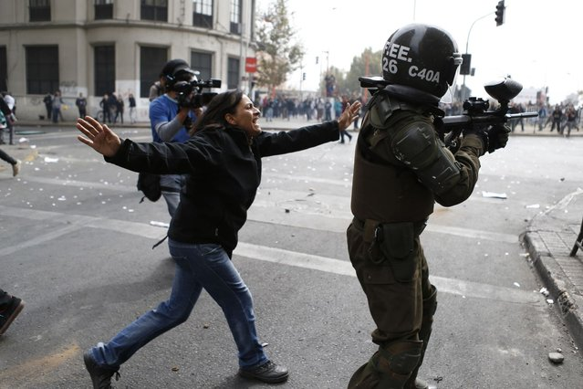 A woman argues with a riot police officer as he uses a paint ball rifle to shoot at student protesters during a rally in which demonstrators demanded that the government make changes to the public state education system, in Santiago April 11, 2013. Chilean students and their supporters took back to the streets in a massive demonstration in demands of free and quality education for all. Thousands of people, led by both secondary and university student organizations, marched through downtown streets in the capital city as they continue to demand an educational overhaul in  the latest student demonstration since the movement began in 2011. (Photo by Ivan Alvarado/Reuters)