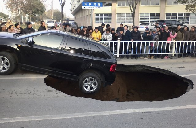 People look at a car hanging on the edge of a caved-in area on a street in Zhenjiang, Jiangsu province December 12, 2014. The street collapsed on Friday morning as the car drove by and formed the pit measuring 2m (6.7ft) in depth and 5m (16.4ft) in diametre, according to local media. (Photo by Reuters/Stringer)