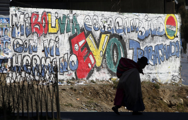 In this October 10, 2014 file photo, a woman carries a bag on her back as she walks past slogans in support of President Evo Morales painted on a wall in La Paz, Bolivia. Morales went on to win re-election under the Movement Toward Socialism Party (MAS). (Photo by Juan Karita/AP Photo)