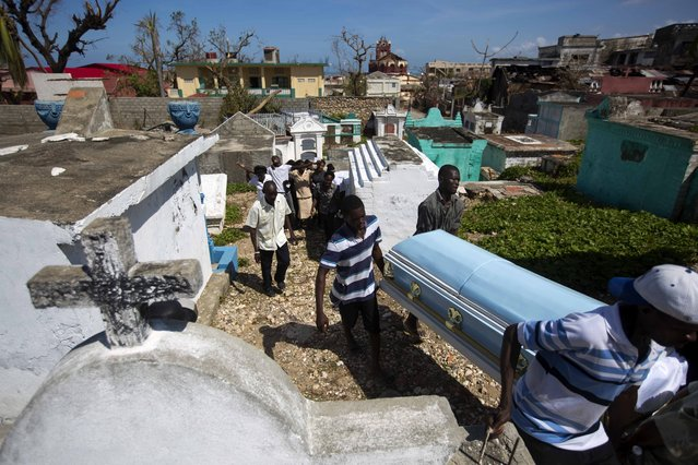 People carry the coffin of Roberto Laguerre to bury him at the cemetery in Jeremie, Haiti, Saturday, October 8, 2016. Roberto, 32, died when the wall of a church next door to his home fell during Hurricane Matthew. (Photo by Dieu Nalio Chery/AP Photo)