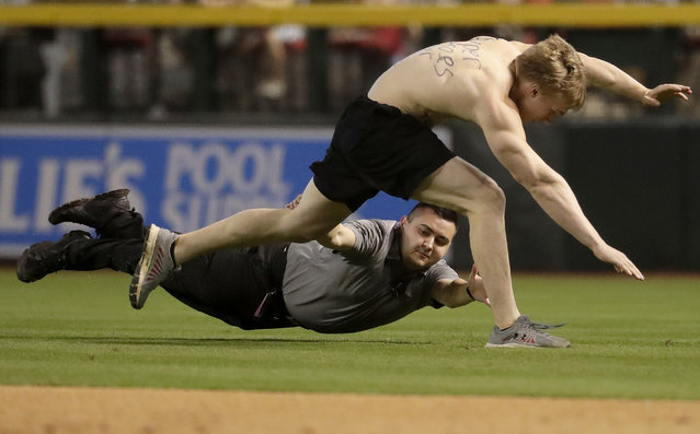 A fan, top, is tackled by security after running onto the field during the third inning of a baseball game between the Colorado Rockies and the Arizona Diamondbacks, Thursday, March 29, 2018, in Phoenix. (Photo by Matt York/AP Photo)