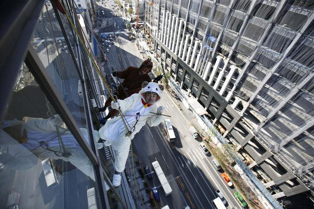 Window cleaners, dressed in horse and sheep (R) costumes featuring animal signs from the Chinese zodiac calendar, work during an event promoting the year-end and new year at a hotel in the business district of Tokyo December 19, 2014. (Photo by Issei Kato/Reuters)