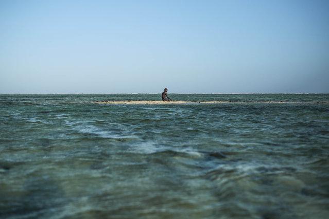 A young Zanzibari fisherman takes a break on a sandbank in the Indian Ocean off the coast of Matemwe village, northeastern Zanzibar, Tanzania, Wednesday, January 28, 2015. (Photo by Mosa'ab Elshamy/AP Photo)