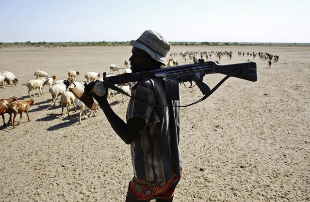 A Turkana man carries a rifle as he herds goats inside the Turkana region of the Ilemi Triangle, northwest Kenya December 21, 2014. (Photo by Goran Tomasevic/Reuters)