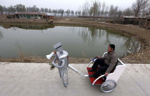 Farmer Wu Yulu, 48, rides in a cart pulled by his walking robot near his home in a village at the outskirts of Beijing April 14, 2010. Hobby inventor Wu, who started to build robots in 1986, has invented 47 robots with different functions like jump, paint, drink, pull cart, massage, and help cooking. He will display more than 30 his robots during Shanghai World Expo 2010, and he wants to promote his practical robots into market by the Expo. (Photo by Petar Kujundzic/Reuters)