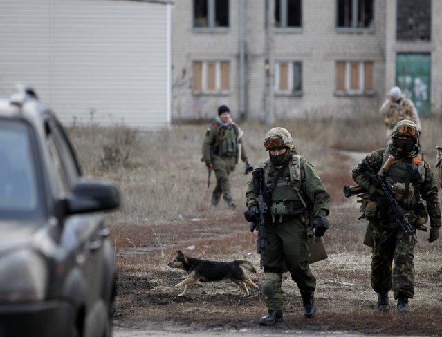 Ukrainian government army soldiers patrol an area in the village of Debaltseve, Donetsk region, eastern Ukraine Wednesday, December 24, 2014. Peace talks aimed at reaching a stable cease-fire in Ukraine between its government forces and pro-Russian armed groups began on Wednesday in Minsk, Belarus, with the discussions to include a pullout of heavy weapons and an exchange of war prisoners. (Photo by Sergei Chuzavkov/AP Photo)