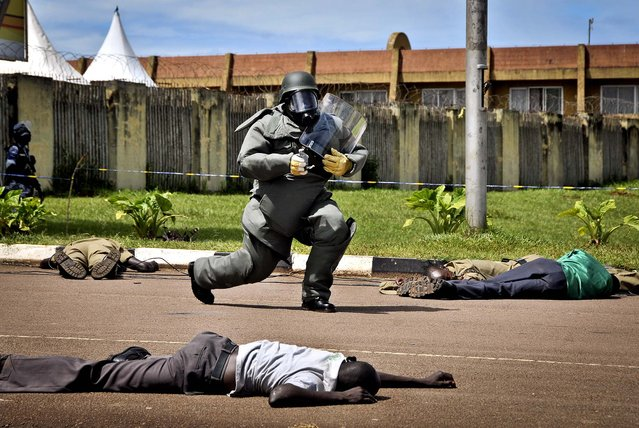 A bomb defusal expert carries a mock explosive device during a counter-terrorist training exercise at Nambole Stadium on the outskirts of Kampala, Uganda, on May 8, 2013. Police officers from the member countries of the Eastern Africa Police Chiefs Cooperation Organisation (EAPCCO) are taking part in a joint multi-national field exercise aimed at testing their response to potential terrorist incidents. (Photo by Stephen Wandera/Associated Press)