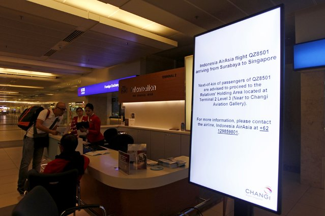 A sign informing the next-of-kins of passengers of AirAsia flight QZ 8501 from Indonesian city of Surabaya to Singapore is seen next to an information counter at Changi Airport in Singapore December 28, 2014. The man pictured at the counter is not the next-of-kin. (Photo by Edgar Su/Reuters)