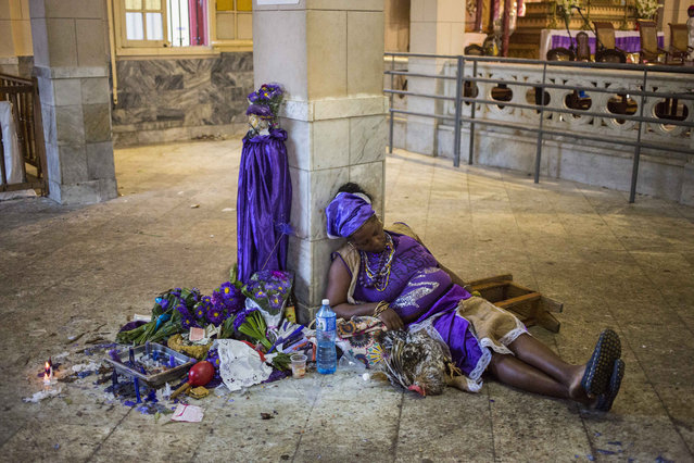 """A woman sleeps amid her candles, flowers and live hen after making her pilgrimage to Saint Lazarus National Sanctuary church, the shrine of """"San Lazaro"""", in honor of the religious icon revered as the protector of the sick, whose statue she placed against the column, in El Rincon, near Havana, Cuba, Sunday, December 17, 2017. The annual pilgrimage draws Roman Catholics, as well as followers of Afro-Cuban Santeria for whom Saint Lazarus symbolizes the deity of """"Babalu-Aye"""", introduced by African slaves brought to Cuba when it was a Spanish colony. (Photo by Desmond Boylan/AP Photo)"""