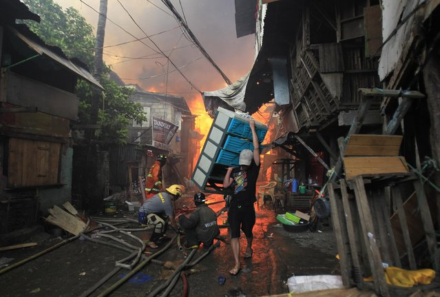 A man salvages his belongings after a raging fire engulfed around 2,000 houses in Quezon city, metro Manila January 1, 2015. At least eight people, including a seven year-old child, died and thousands were displaced after a fire broke out in different locations in metro Manila as the New Year kicked off, local media reported. (Photo by Romeo Ranoco/Reuters)