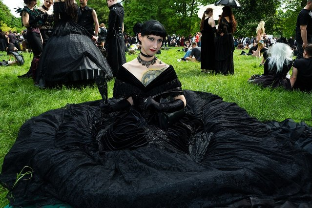 A woman in a black dress sits on the lawn during the traditional park picnic on the first day of the annual Wave-Gotik Treffen, or Wave and Goth Festival, on May 17, 2013 in Leipzig, Germany. The four-day festival, in which elaborate fashion is a must, brings together over 20,000 Wave, Goth and steam punk enthusiasts from all over the world for concerts, readings, films, a Middle Ages market and workshops. (Photo by Marco Prosch)
