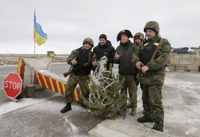 Ukrainian army soldiers pose for photo with volunteers at a check point in Debaltsevo, Donetsk region, Ukraine, Ukraine Sunday, December 28, 2014. Volunteer groups across Ukraine are raising funds and buying equipment for soldiers fighting in the east of the country against pro-Russian separatists and often delivering the supplies directly to the soldiers themselves. In Kiev alone, some 30 volunteer groups involve several thousand people. (Photo by Efrem Lukatsky/AP Photo)