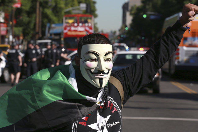 """Los Angeles: A supporter of the Anonymous movement wearing a Guy Fawkes mask marches on Hollywood Blvd as part of the global """"Million Mask March"""" protest in Los Angeles, California November 5, 2014. (Photo by Jonathan Alcorn/Reuters)"""